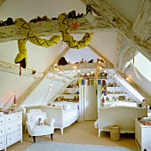 A child's attic room with rustic wood beams equipped with white furniture