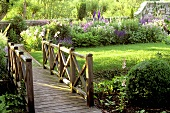 A wooden bridge with a railing over a stream in a flowering garden