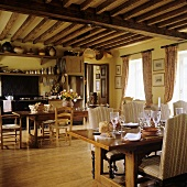 A set table with upholstered chairs in an open plan kitchen under rustic timber beam ceiling of an old country home