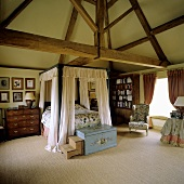 A four poster bed in the attic of a country house with rustic wood beams
