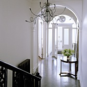 Medusa chandelier in an elegant stairwell with rounded arches and a view of a antique side table in an entrance to a home
