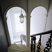 A steep flight of stairs with archways at the bottom with a view of a ceiling lantern