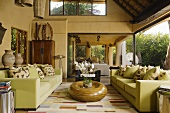 A light green sofa and a wooden floor table in front of a window in a South African villa