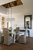 Wicker chairs around a laid table with a crystal chandelier hanging above it