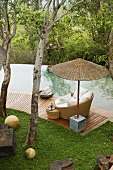 South Africa - bamboo shades and wicker chairs on a wooden terrace by a pool in a garden