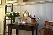 An antique wall table and a wooden ladder against white wood panelling