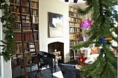 A fireplace room with a bookshelf and a decorated Christmas tree