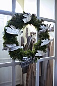 Silver angels on a Christmas wreath hanging on a glazed door to a cloakroom