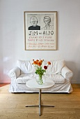 Flowers on a bistro table with metal base in front of a white sofa and a drawing on the wall