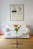 Blumen auf Bistrotisch mit Metallfuss vor weißem Polstersofa und Zeichnung an der Wand