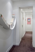 A narrow, illuminated hallway - a curved wall shelf and a blackberry-coloured carpet