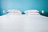 A bed with white bedclothes and pillows against a blue wall