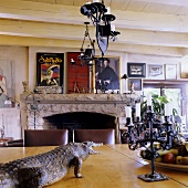A dining room with wood beam ceiling in a South African country house - a stuffed crocodile and a chandelier hanging above a table