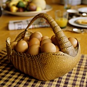 An animal skin basket of eggs on a checked cloth