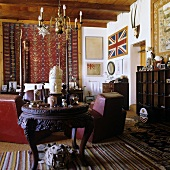 A living room in a South African country house with a dark antique table and a chandelier hanging from the wooden ceiling