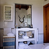 A bathroom in a South African country house - a stone wash stand with a mirror on a white, mosaic-tiled wall