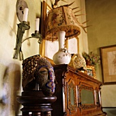 Table lamp with fabric shade on an antique wooden cabinet and painted bust made of wood
