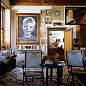 Family portraits on the wall and antique chairs in a living room of a South African country house