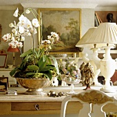 White orchids in a silver bowl and white table lamps on a wooden table