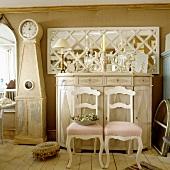 Zwei weisse ländliche Stühle vor Buffet aus hellem Holz mit Kerzenleuchtern im Vorraum