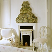 A white armchair and a white chair in front of a fireplace with wall decoration in a bedroom