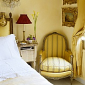 An antique armchair next to a bedside table with a lamp with a red shade in the corner of a bedroom