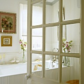 An open bathroom door with a view of a white bathtub and pictures in gold frames hanging on the wall