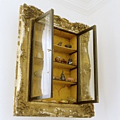 A cupboard with open glass door surrounded by a picture frame