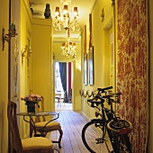 A bicycle, wooden chairs and an occasional table in a narrow hallway with yellow walls and chandeliers