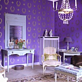A living room with a Rococo chair and a country house-style wall table against a wall hung with purple and gold wallpaper