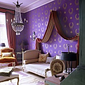 An antique sofa-bed with a canopy against a wall papered with purple wallpaper with a gold pattern