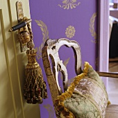 Silk pillows on a vintage wooden chair in front of purple wallpaper with gold colored Oriental pattern