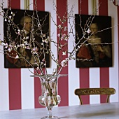 A flowering sprig in a glass vase in front of a red and white striped wall hung with pictures