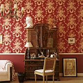 An antique wooden davenport against a wall papered with decorative red and white paper