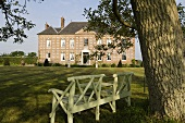 A wooden bench under a tree and a view across a garden to a French manor house