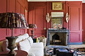A red wood panelled fireplace room with a white two seater sofa
