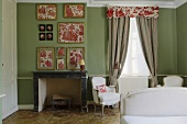 A bedroom with a fireplace and frame pieces of floral fabric on a green wall
