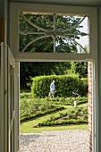 A view through a door into a garden and a gardener tending borders