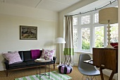 A black leather sofa, a white floor lamp and a curved window bank with a view