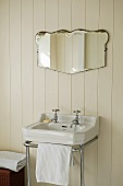 A wash basin with a chrome towel rail and a mirror on white wood panelling