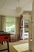 A boy's bedroom - a Union flag on a surf board next to a window with a view