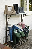 Wellie boots on a rack against the wall of a house