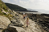 Walking with children on a rocky path by the seashore