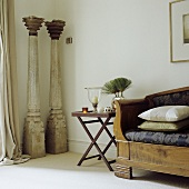 A delicate side table next to a wooden bench and decorative, antique pillars in a corner of a living room