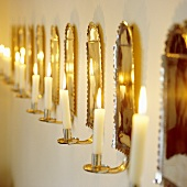A romantic atmosphere - burning candles in brass-coloured wall holders