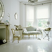 An elegant living room with a bay window and Rococo style chairs on a white painted floor