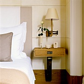 A bedside table with a drawer and a dark wooden foot in front of a white wood panelled wall