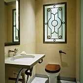 A designer washstand, a mirror and a toilet in a renovated bathroom