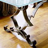 A metal table leg on parquet