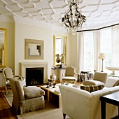 An elegant room with a fireplace, various types of seats and and chandelier hanging from the stucco ceiling